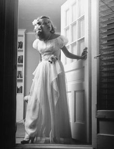 1950 Student waits at the door for her prom date,...