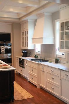 range hood // countertops // floors // glass front cabinets w/two closed cabinets above // grey walls // hardware // bin pulls // symmetrical windows // molding
