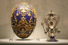 """1912 The """"surprise"""" inside is a Russian double-headed Imperial eagle with a miniature portrait of the Czarevich Alexis, set in platinum and encrusted with diamonds. The Imperial eagle holds the orb and sceptre representative of the Romanov crown jewels. The intricate frame sits on a lapis lazuli base and can be completely removed from inside the egg.  Inside the egg, an engraved golden disc with a rose window design serves as a platform for the portrait frame. #Faberge"""