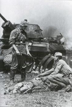 One of the most emblematic pictures of Kursk...a WaffenSS soldier tries to help a wounded Russian...behind lies the T-34 tank burning...