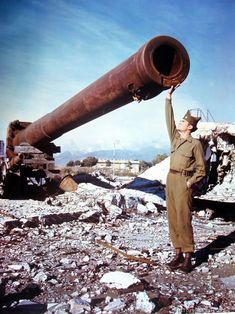 The long barrel of a 16 inch coastal defense gun looms large to the Private standing in front of it. The gun was rendered useless by retreat...