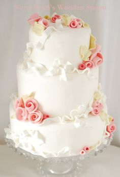 Romantic Rosettes - With windswept whimsy and an air of romance, this fondant wedding cake is dotted with bunches of sugar roses and strewn with sugar ribbons that dance across the cake and tantalize the eye. - http://www.nanapearls.com/gallery.html#