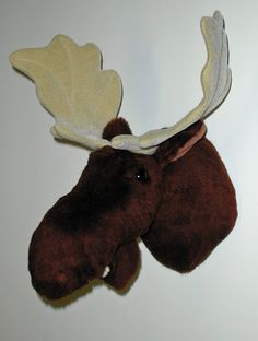 "Plush Moose Head ""Shorty"" Medium Shoulder Mount. Shorty's plush fur is a soft short pile. He has deep fuzzy nostrils, and a fixed lower jaw complete with teeth and tongue. His eyes and his antlers are almost too big for his head. But if you want a tough almost comical looking moose, he's perfect! PRODUCT SPECS: Ready to hang. Shorty's depth is 13"" from nose to wall. Adjustable antler span is 16"". Girth at shoulder is 23""."