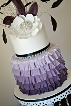 wedding cake with feathers, flowers and purple ombre ruffles.