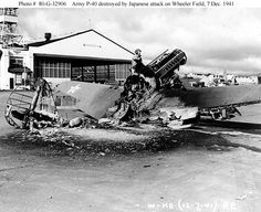 Men examine the burned-out wreckage of a P-40 pursuit aircraft, near Hangar 4 at Wheeler Air Field, following the end of the Japanese raid on 7 December 1941. Note long blast tubes for the plane's nose machine guns.