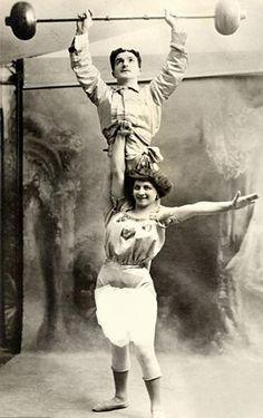 A strongwoman holds her partner aloft, c. 1910