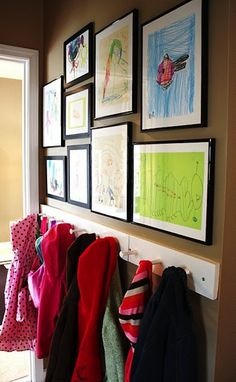Gallery wall of kids art above a coat rack in mudroom...this could work for you if we transform closets across into locker area