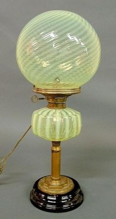 An (unattributed) green swirl Vaseline opalescent glass oil lamp, Circa 1880, with black onyx baseglobe shape shade. Electrified