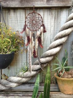 dreamcatcher- brown leather weave with copper and silver beads, maroon feathers, large turkey featherscream leather fringe by Sailor's Omen. $108.00, via Etsy.