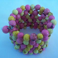 pulseira de mola feita com sementes de açaí rosa com amarelo. R$3,50