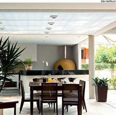 A varanda gourmet, com churrasqueira e forno de pizza, tem iluminação zenital que passa pelo pergolado metálico com cobertura de policarbonato. Projeto do escritório Reinach Mendonça.