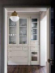 Love the shaker cabinet and the location/style of the pulls. Courtney Hill Interiors - Butler's pantry, glass fronted cabinet with wallpapered cabinet interior, gray kitchen cabinets with brass hardware, brass and opalglass Hicks pendant, Glass Front Cabinets, Grey Cabinets, Kitchen Cabinets, Kitchen Doors, Home Interior, Kitchen Interior, Interior Design, Interior Office, Classic Interior