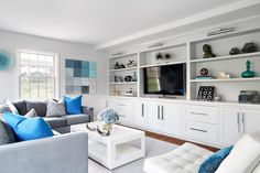 Cool colors evoke a feeling of tranquility in this lovely living room. A wall with built-in shelving is the perfect place to house the TV, books and others decorative items to make the space feel more homey. A gray sectional provides plenty of seating without overcrowding the space.