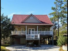 LOVELY BEACH HOME in the desired wooded section of Oak Island.  Sit on the huge front porch or on the back screened porch and listen to the waves of the ocean.  No flood insurance is required at this location.  This house features a beautiful red metal roof.  A large master bedroom with his and her closets plus a master bath with a walk in shower and a Jacuzzi tub.  Cathedral ceilings in the living room flowing into a spacious dining area and kitchen.  All new stainless steel appliances…