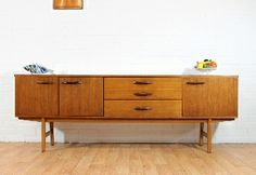 Stunning Teak 6.5ft Credenza/Buffet by I think Avalon of BritainCirca 1960\'sOffered is a stunning 6.5 ft Teak Credenza by we think Avalon of Britain.Modern sleek design with Beautiful grain, leg detail and handle detail.Features double doors on one side , a single cupboard on the other side with 3 drawers in the middle. Lined top drawer with separators.Measurements:Width: 80 inchDepth: 17.5 inchHeight: 28 inchThis is one of many pieces we are importing from Europe. Please message me if you…