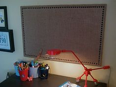 I recovered my son's bulletin board but never really liked it so I wanted to give it a more rustic manly appeal. Using burlap, black upholstery tacks and my trusty staple gun.