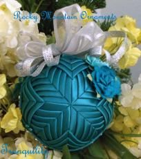 Tranquility Quilted Ornament--This 3 inch ornament is layered in the Cathedral pattern with teal satin ribbon. The top is embellished with sheer silver ribbon. The sides are embellished with different colored teal paper roses. The sides are wrapped with a crystal ribbon. Gift boxed,  $25. (Designer's original description, edited by me. What a beautiful ornament!)