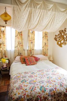 Bohemian bedroom - golds, orange, yellow, red green Fabric over bed (tone down the harsh overhead light.