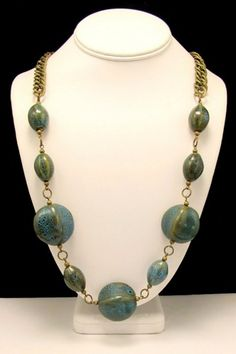 This necklace combines different shapes of blue/brown porcelain beads to create a chunky and beautiful piece. They are suspended from a heavy antique brass chain. It measures 27 inches long.  I stand
