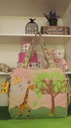 Bolsa Maternidade com tema de Girafa. <br>Confeccionada em tecido de sarja e tricoline, estruturada com manta resinada, quiltada e forrada com tecido de algodão. <br> <br>Dentro da bolsa tem 4 divisões, no verso um bolso com ziper, aplicação de girafa, lateral com bolsinhos. <br>Alça transversal removível. <br>Frente da bolsa com aplicações no tema Girafa e Árvore. <br>(Pode ser feita em outros temas e cores) <br> <br>AO FAZER SEU PEDIDO INFORME O NOME QUE SERÁ BORDADO. <br> <br>FEITA SOB…