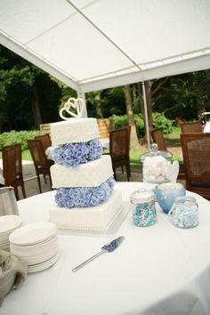 Bruidstaart vierkant en wit met royal icing. 2 harten boven op en echt hortentia's