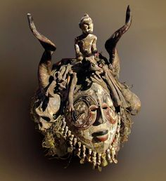 artafrica: Igbo mask, Nigeria. It represents a maiden spirit and probably belonged to a hunting fraternity. It is topped with a statuette and the skull of a goose. It is also heavily empowered with, among other items, beads, coins, bells, shotgun shells, skulls, horns, and bones.