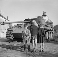 Three French boys looking at a knocked-out German Panther tank in the Falaise pocket, Normandy, 25 August 1944.