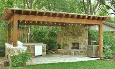 Outdoor fireplace and built in grill under an arbor
