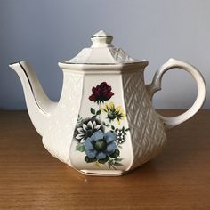 Sadler Vintage Teapot This is a lovely Sadler teapot with basketweave embossed panels and panels with transfers of darker flowers and foliage. The flowers are blue, yellow, dark pink and white with green leaves. This is a wonderful teapot for serving tea, it holds 5 cups. (1.25L) This