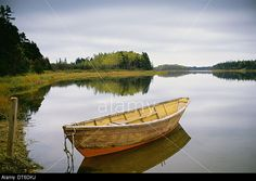 A small wooden dory or rowing boat moored on flat calm water, in Savage harbour on Prince Edward Island in Canada. Stock Photo