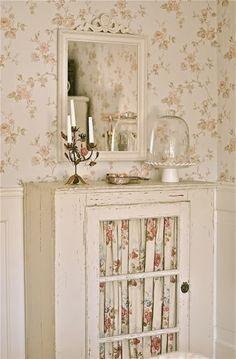 Wainscoting with floral wallpaper, painted white cabinet with vignette on top, and a pretty mirror