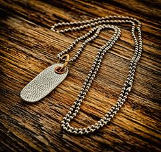 Good Impressions! necklace in textured pewter with a copper rivet by Q. Miller Handmade Jewelry. American Made. See the designer's work at the 2015 American Made Show, Washington DC. January 16-19, 2015. americanmadeshow.com #necklace, #jewelry, #pewter, #copper, #texture, #americanmade