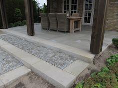 ... een betontegel grijs 100x100cm. Aansluitend is een trap gemaakt van betonnen traptredes grijs met aan de binnenkant portugees granieten kinderkoppen.