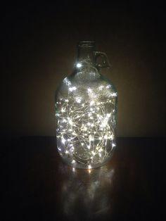 I have five brown jugs  that I can tie in together and make an amazing light source in the middle of Canopy...or could make separate ones for trees, etc...Glass gallon jug light by Justthewoods on Etsy, $35.00