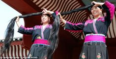 China | The Red Yao people believe a woman's long hair brings longevity, wealth and good fortune.  These two women are about to demonstrate the ancient art of the 'up do', twisting and wrapping their jet black hair