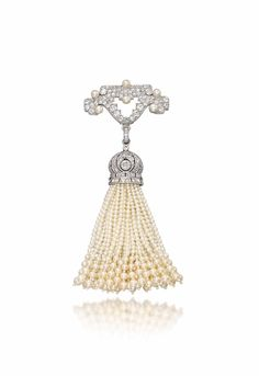 A BELLE EPOQUE PEARL AND DIAMOND BROOCH, BY CARTIER -  The pavé-set geometrical top with pearl accent suspending a detachable seed pearl tassel pendant with diamond-set openwork cap, 1910s