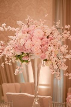 Captivating blossoms splaying and spilling overtop tall vase edge. Placed high enough so as not to discourage table cross-talk.