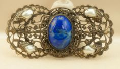A lovely old Czech brooch with pearls and blue glass center cabochon on a floral motif lattice background. The metal is probably brass.
