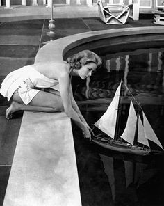 """Grace Kelly in white dressmaker bathing suit designed by Helen Rose for the film """"High Society"""" here in a scene with a model of the True Love, 1956"""