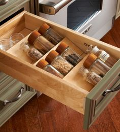 Possible to employ this idea since our bottles, although square, should fit.  Just need room for 40+.  Like storage space for pinch bowls or even measure or funnel at rear of drawer.  Unusual containers, like vials of vanilla beans could go there, too.