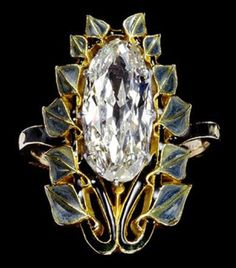 René Lalique Diamond ring. The large diamond is set vertically along the bezel, framed within a border of green leaves on black stalks, with the shoulders also enamelled dark green. By René Lalique c.1902-4.