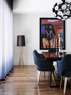 Прекрасный проект Laurel Court от Sisalla Interior Design. В данной столовой выделяется деревянный стол на мощной металлической опоре, темно-синие мягкие кресла и светильник, напоминающий брутальный одуванчик.