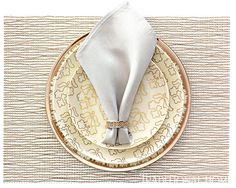 "Napkin in gray, ""Basketweave"" napkin ring, and white/silver ""Basketweave"" placemat, all from Chilewich. ""Opal"" dinner plate and ""Trellis Opal"" salad and bread plates by Kim Seybert through DeVine Corporation. - Photo: Peter Krumhardt"