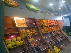 Inside of KIN Fruit Shop. Racks full with all type of fresh fruits (mangoes, apples, grapes, peach, oranges etc)