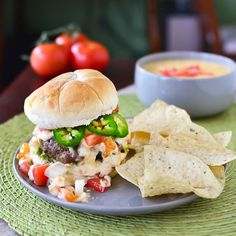 Tex-Mex Burger -- a juicy burger topped with guacamole, spicy homemade queso sauce, pico de gallo, and fresh jalapeno slices.