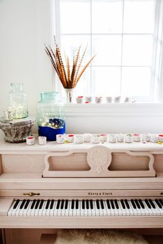 How cute is this candy bowl advent calendar?! Ceramic cups filled with sweets and adorned with hand-painted numerals make for a fun countdown atop the pickled mahogany piano.
