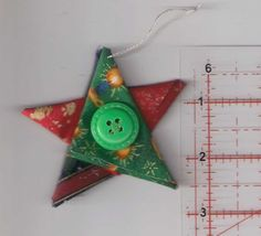 Sometimes Id like to have Christmas year round. Failing that, I look forward to Christmas in July :) And its never too early to start planning for next Christmas!  A set of five Christmas tree ornaments in the shape of stars, created from a variety of folded Christmas fabrics in red, blue, green, white, silver and gold. They have a silver hanging loop, and a red vintage button in the centre. Each star measures approximately 7.5cm (3in) tall/wide and the hanging loop is approximately 4cm…