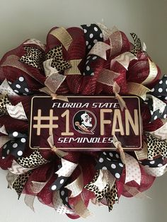 "Florida State Seminoles Mesh Wreath. This wreath is made on a maroon mesh. It features a Florida State Seminoles centerpiece surrounded by lots and lots of gold, white and black high quality wired ribbons. This wreath measures approximately 23"" in diameter. What a great way to show your support for your favorite team and to welcome your friends and family to your home."