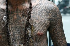 A motorcycle taxi driver in Bangkok, Thailand showing his sacred sak yant tattoos