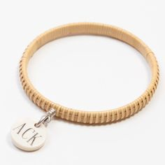 "ACK Basket Weave Bangle - Inspired by the iconic Nantucket Lightship basket, this natural colored bracelet is constructed of cane, handmade by local Nantucket basket weaver Janet Carreau. This bracelet is embellished with an engraved fossilized mammoth ivory charm-a map of Nantucket on one side and ""ACK"" (Nantucket airport's call letters) on the other side. A gift to remind your loved one of their favorite place."